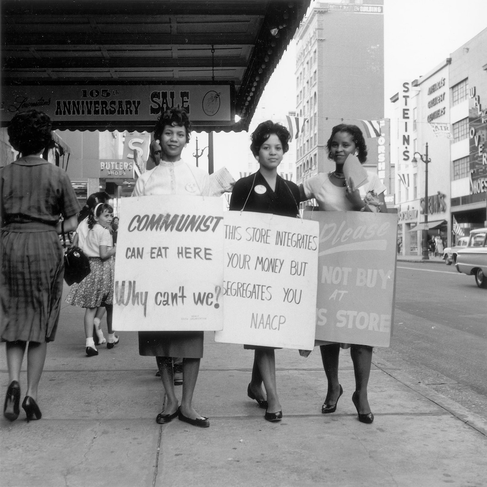 three women standing holding signs